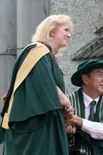 Kathy Axcell wearing a green graduation gown, accepting an award