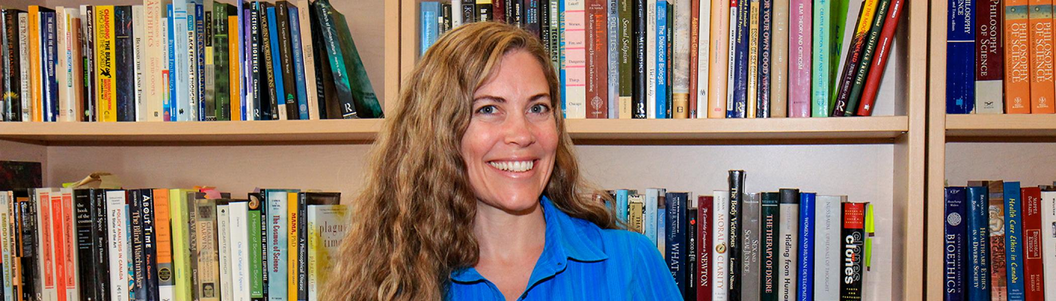 Dr. Moira Howes smiling at the camera in front of a bookcase of books