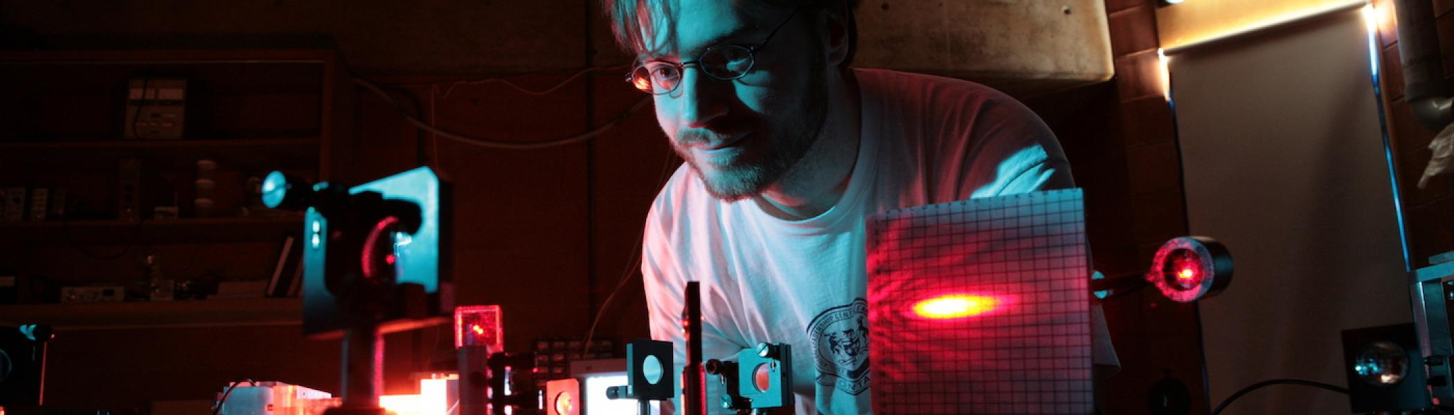 A male student looking down at some electronics on his desk in dark red lighting