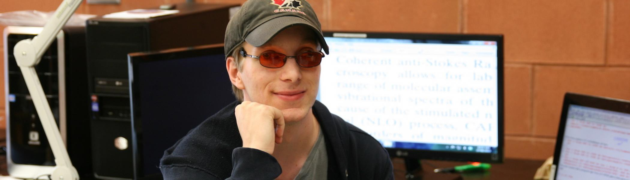 A student wearing sitting in front of a computer with his chin resting on his hand and smiling