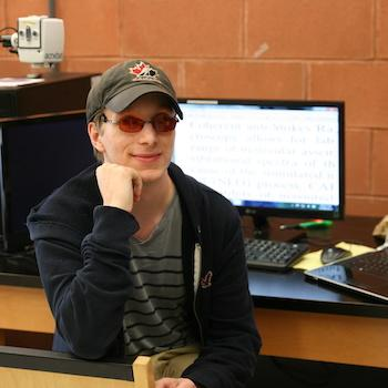 A student sitting in front of a computer with his chin resting on his hand and smiling