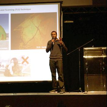 A presenter standing in front of a big screen giving a talk