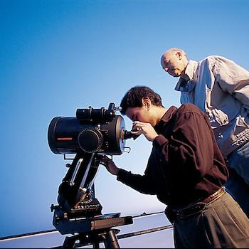 A student looking into a telescope with a professor behind him looking at the sudent