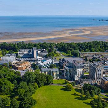 Aerial view of Swansea University, with buildings and a green wooded area right on the coast.