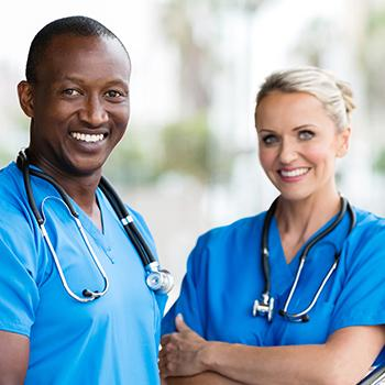 two doctors standing beside another both dressed in blue
