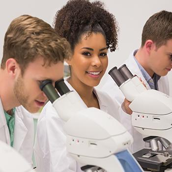 4 doctors are sitting by microscopes one doctor is looking up at the camera smiling