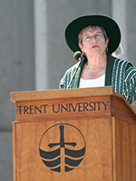 Dr. Bonnie Patterson speaking at a podium outside Bata Library during Convocation ceremonies