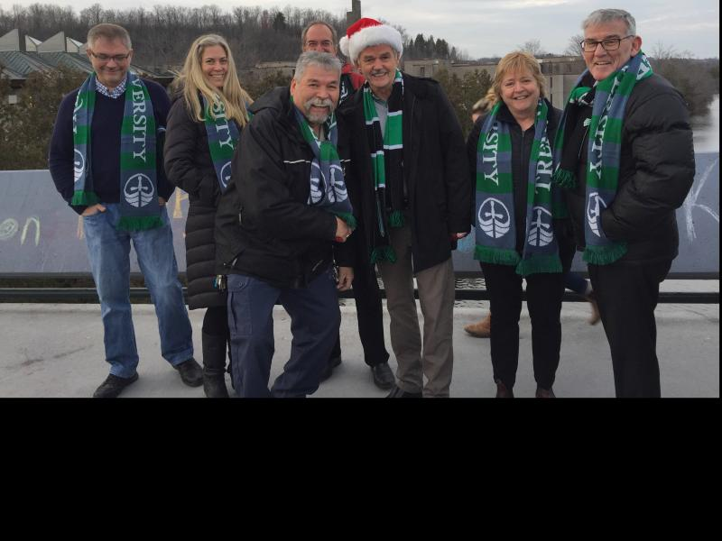 Dr. Leo Groarke with fellow staff members all wearing their Trent Scarves and taking part in the Trent holiday greeting video shoot on the Faryon Bridge.