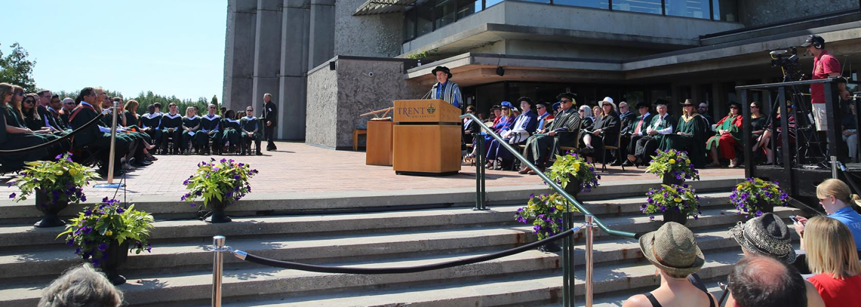 Dr. Leo Groarke standing talking into a podium microphone during convocation outisde of the Bata library