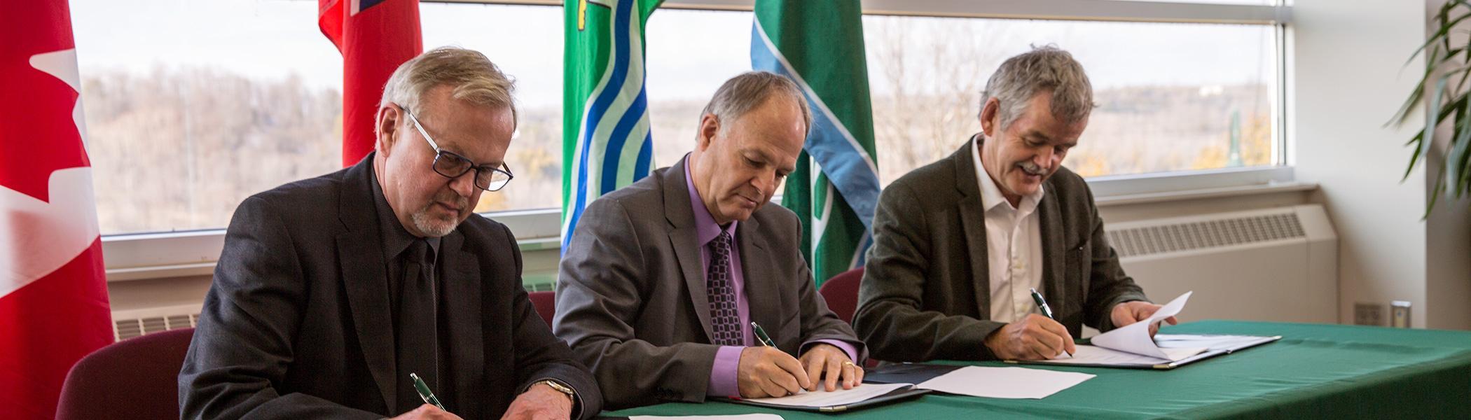 Three men signing an agreement