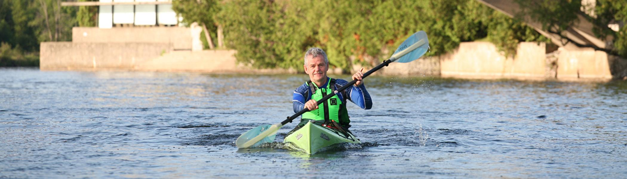 Dr. Leo Groarke kayaking on the Otonabee river in front of the Bata Library