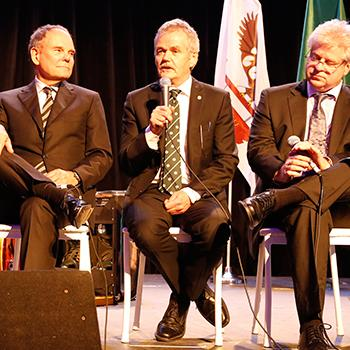 Dr. Leo Groarke sitting on stage in between Dr. Don Tapscott and Linwood Barclay speaking into a microphone