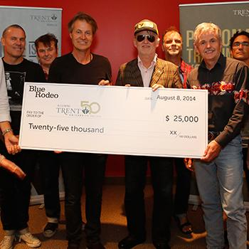 Dr. Leo Groarke holding a large white check for $25,000 with the band Blue Rodeo in front of a red wall during the 50th anniversary festivities