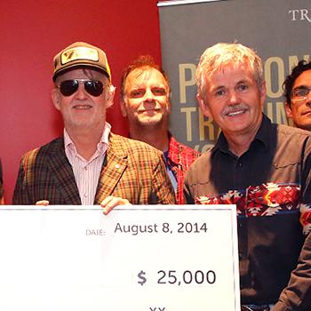 Dr. Leo Groarke, Julie Davis and Lee Hays posing with a large white check for $25,000 with the band Blue Rodeo in front of a red wall