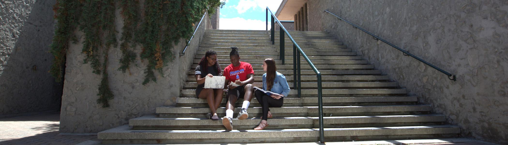3 students sitting on steps outside working on a laptop