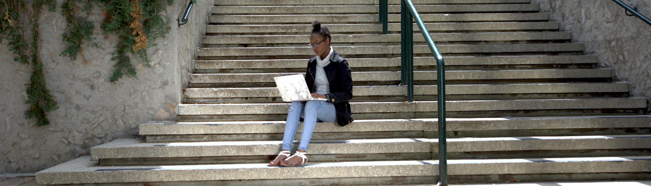 A student working on a laptop outside on stairs