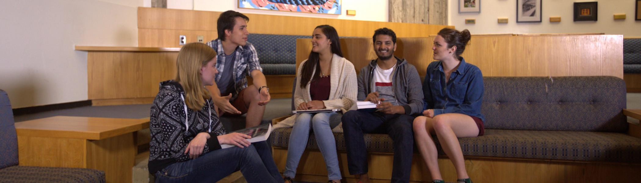 A group of students sitting on a sofa talking to each other