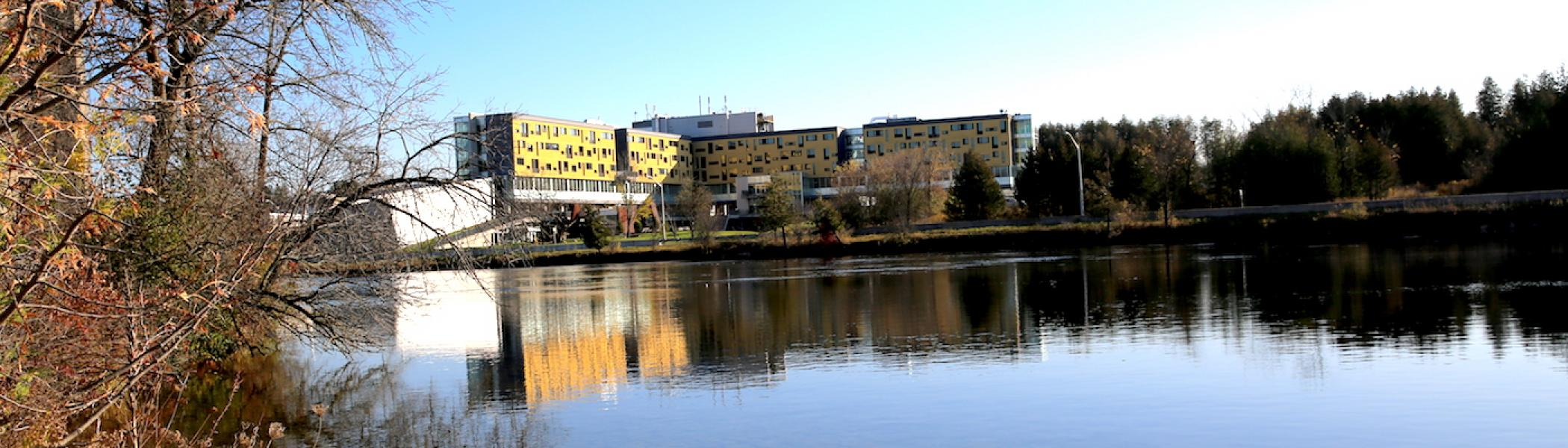 An exterior view of Gzowski College with the river in front of it