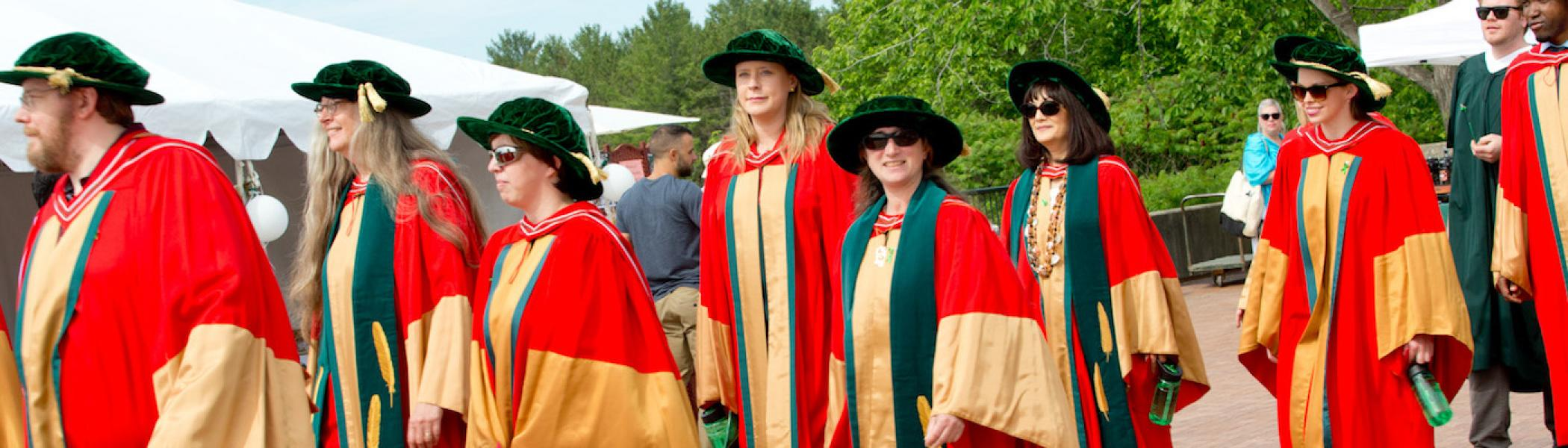 A group of graduate students walking in a line on convocation