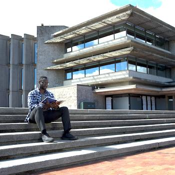 A guy sitting on the steps of Bata Library reading a book