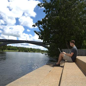 A guy sitting on steps by the river working on his laptop