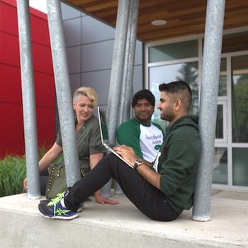 3 students sitting outside at Trent Durham