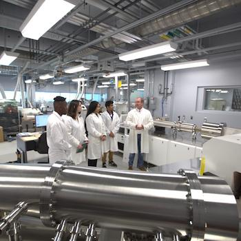 A group of students in lab coats standing with a professor in a lab