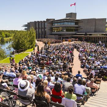 A crowd of people sitting in front of Bata Library during a convocation ceremony