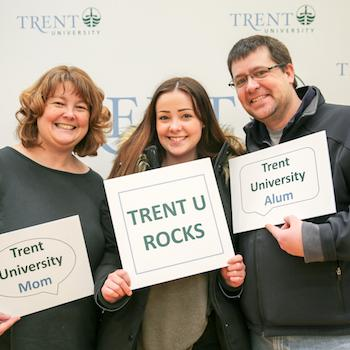 A girl standing between her parents at Trent University