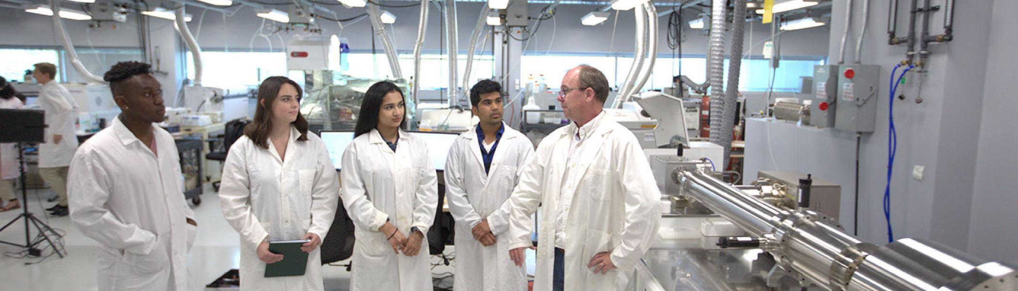 group of students and professor in lab coats in the water quality centre