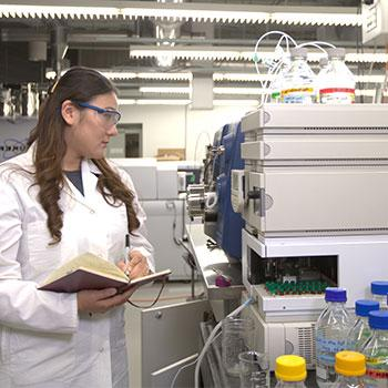Scientist holding book and writing down results from equipment containing many vials