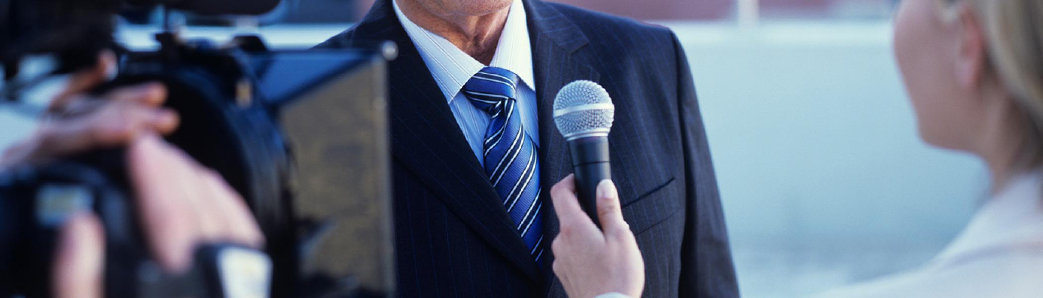one man in a suit is talking to several microphones