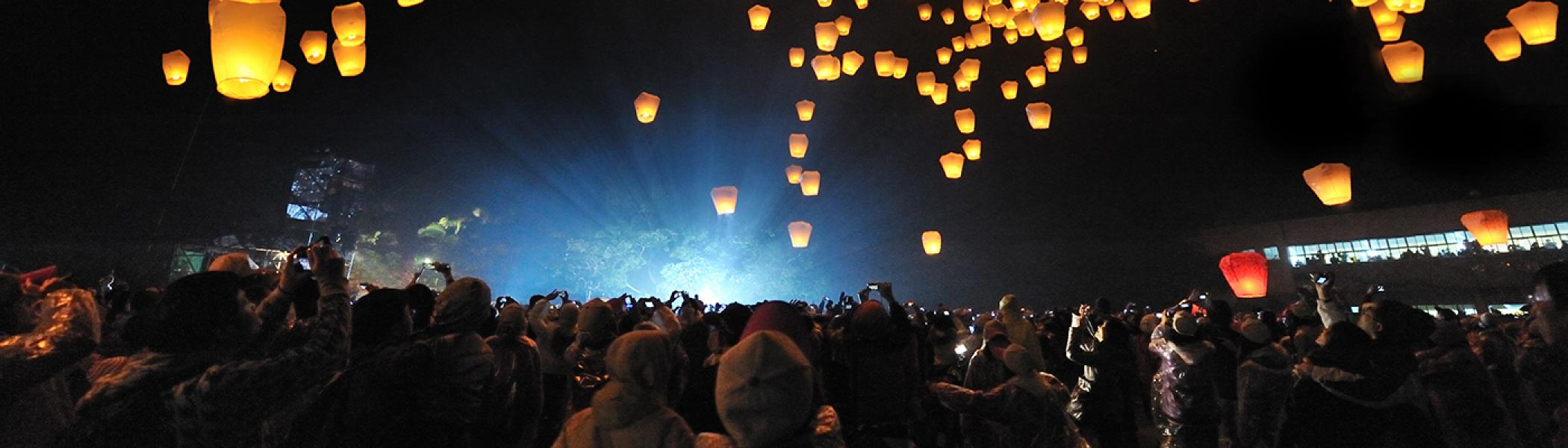A crowd of people staring up a candles flating in the sky at night
