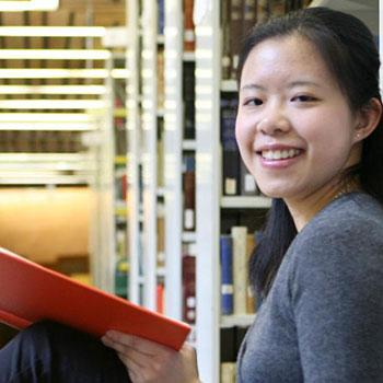 Student sitting in library looking at camera