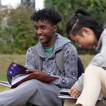 Students sitting on grass, laughing and looking at books