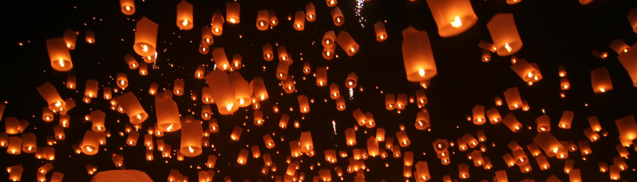 A crowd of people letting go of lanterns