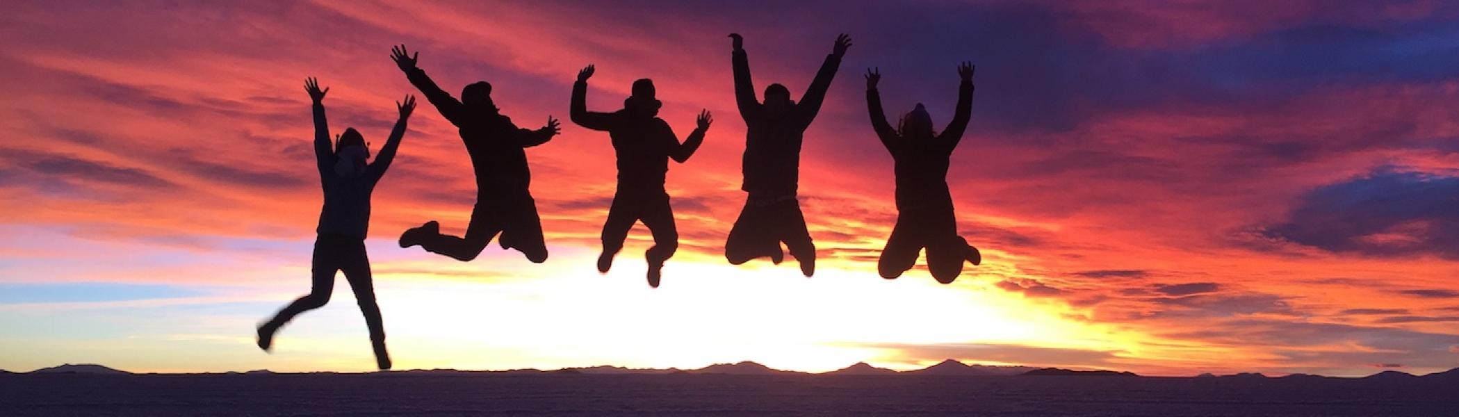 A group of people jumping in the air with a sunset behind them