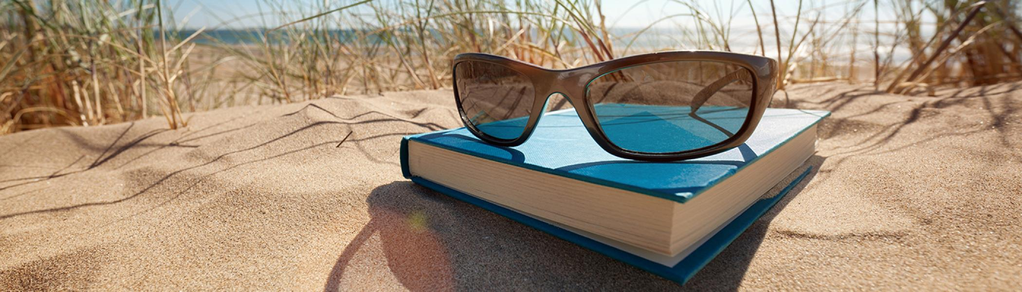 A pair of sunglasses resting on a blue book on a sandy beach in front of the ocean