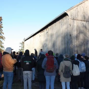 group of people standing outside a barn