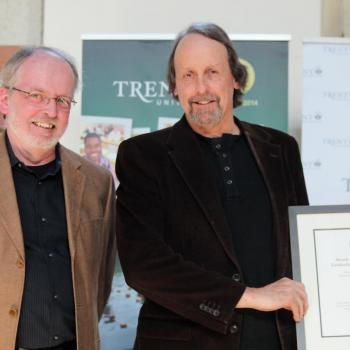 2 men smiling at camera, one of them Professor Tom Whillans receiving teaching award