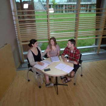 3 students sitting a table conversing