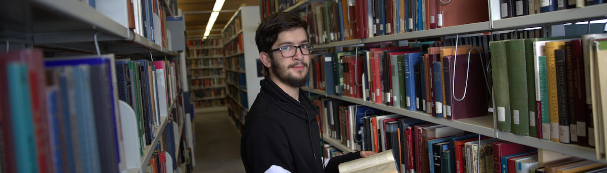 A guy holding a book and standing between bookshelves in the Bata Library.