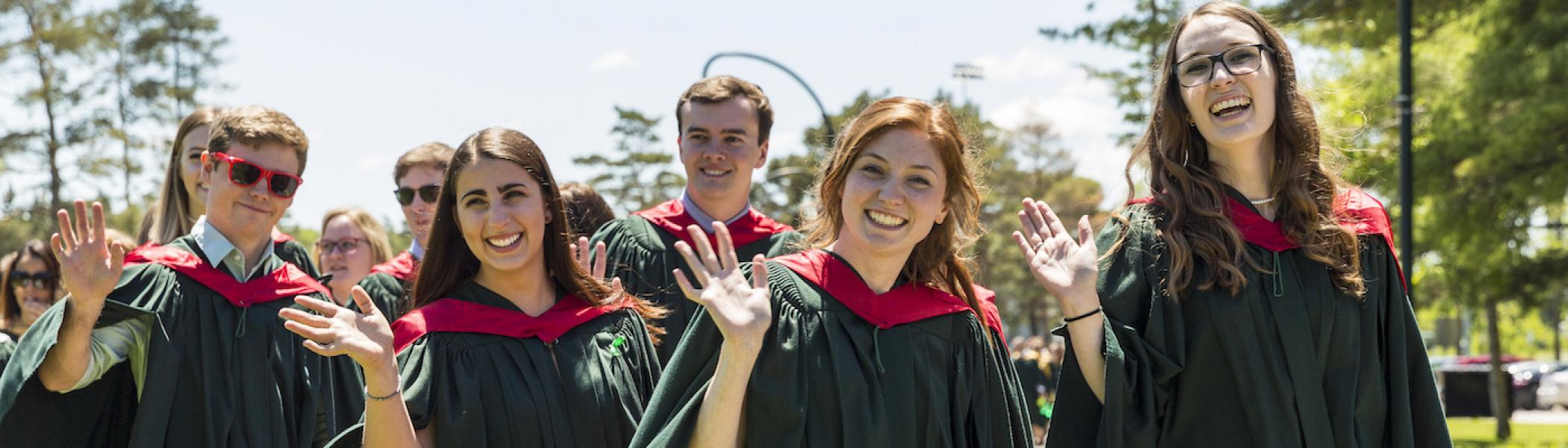 A group of students at their Trent University convocation wearing gowns and smiling.