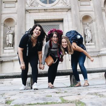 Three girls wearing big backpacks smiling in front of a building in Europe