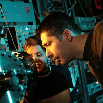 Two researchers studying an instrument at the Trent Centre for Materials Research