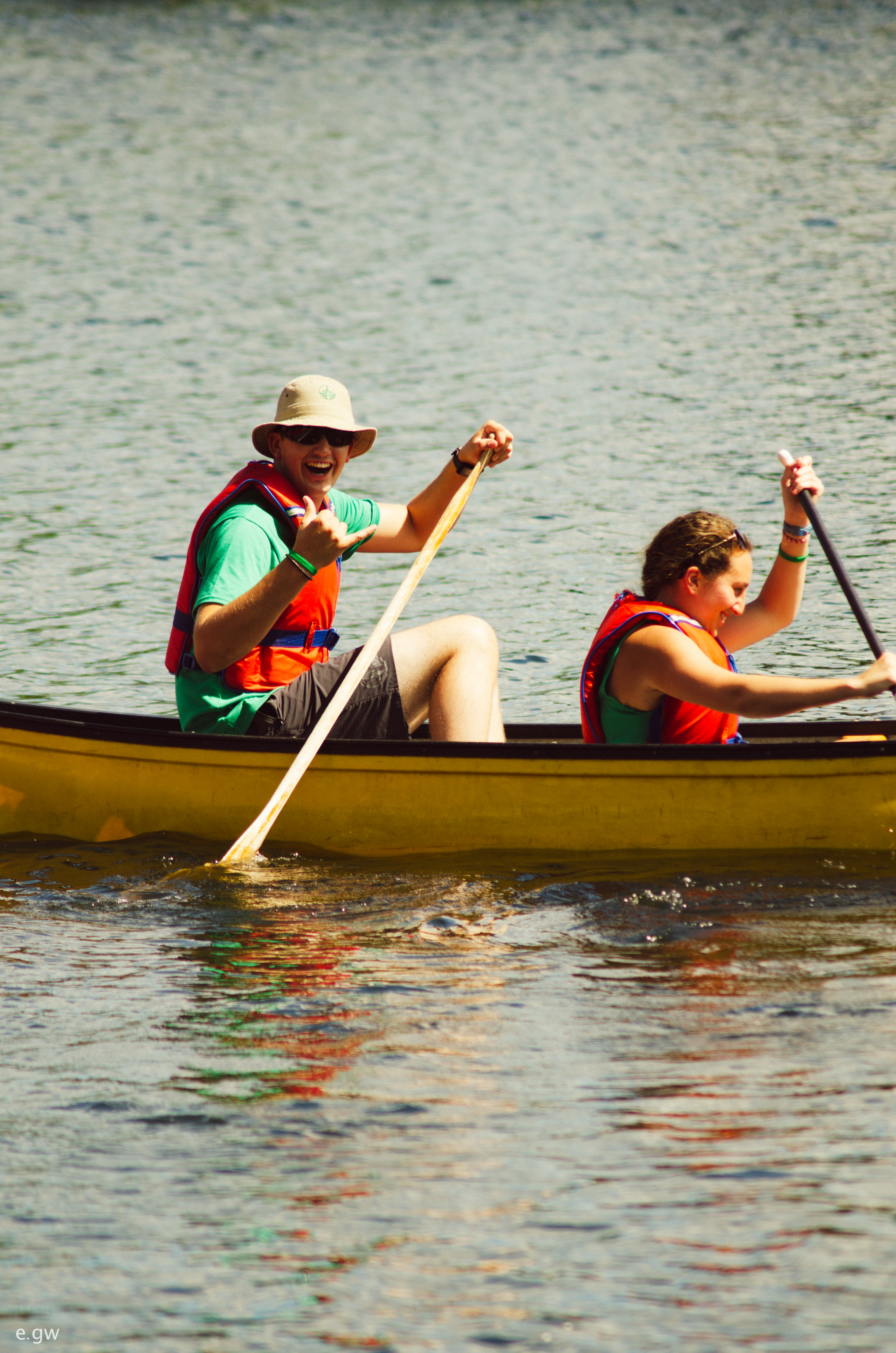 Image of student and student leader in a canoe, paddling and smiling