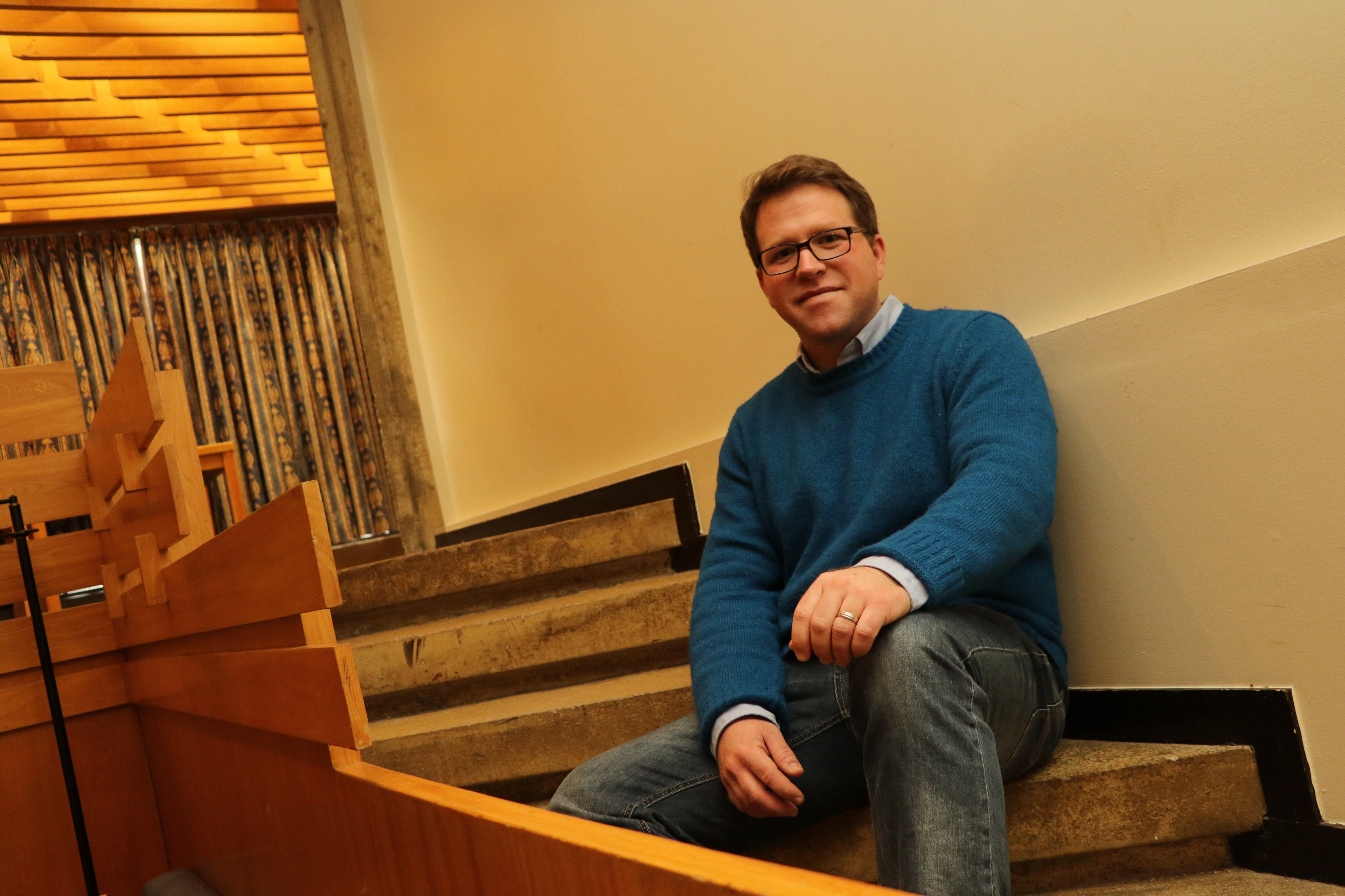 Michael Hickson sitting on steps in 'The Pit' in Champlain College