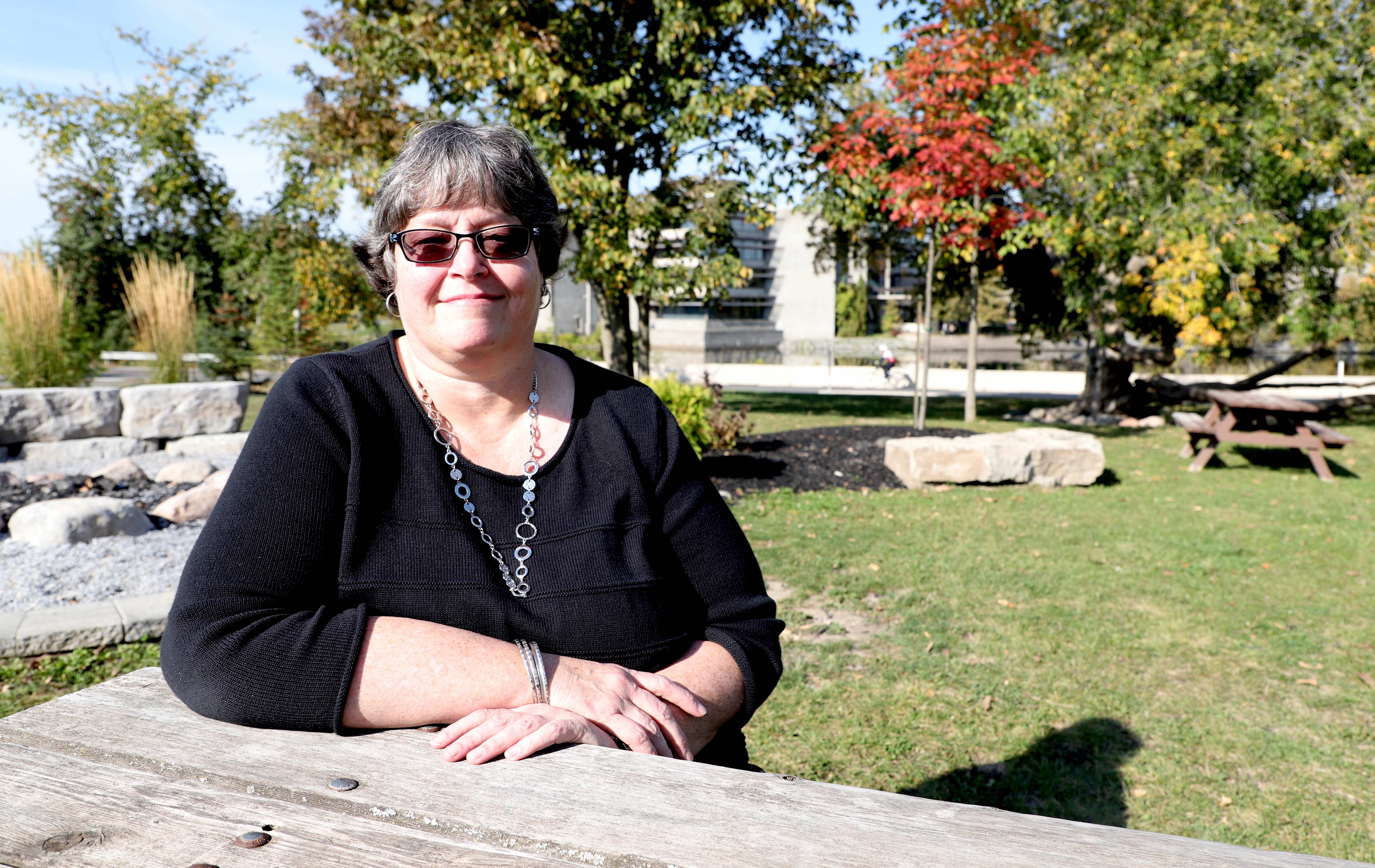 Deb Earle sitting at picnic table with Bata Library in the background and trees