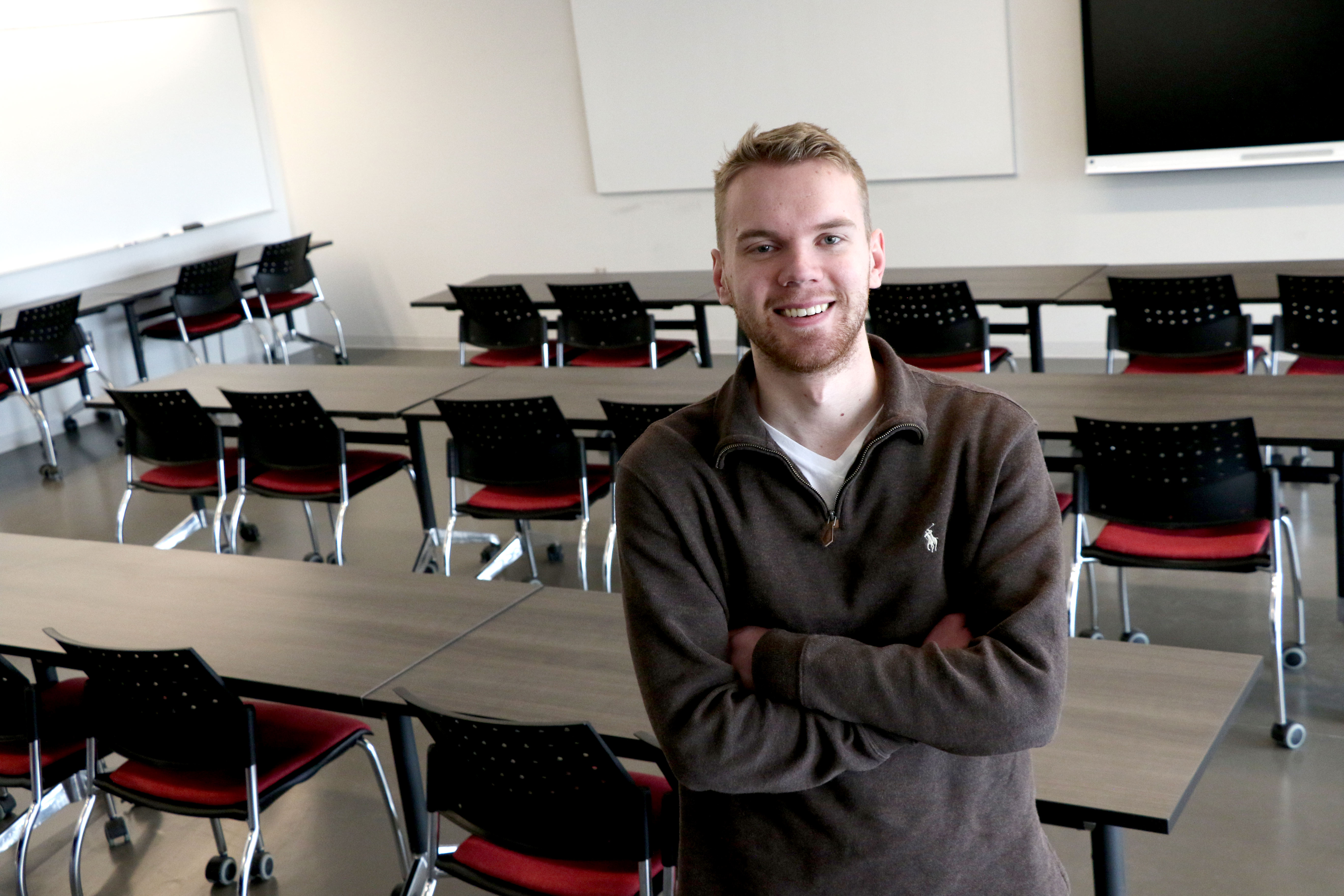 Philosophy student Drake Sullivan posing with arms folded, smiling, in student centre classroom