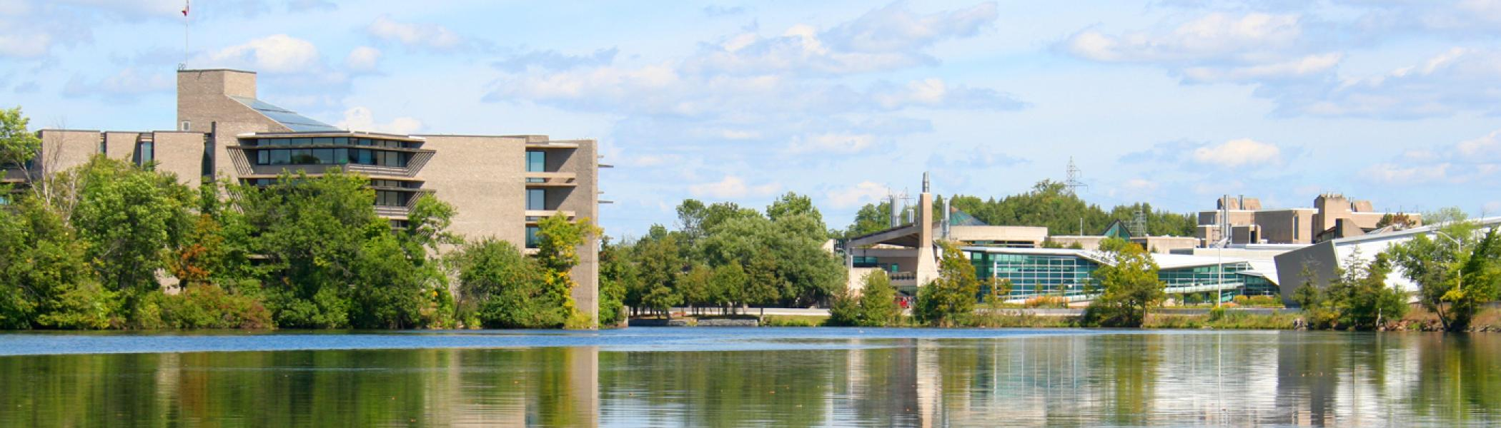 Trent University's Peterborough Campus from down-river highlighting Bata Library and the bridge.
